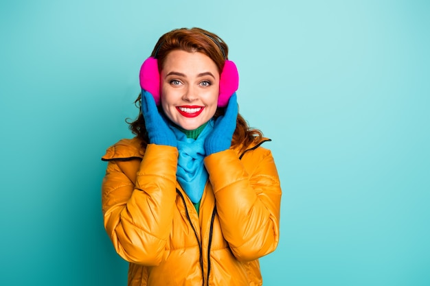 Portrait of charming cute girlish woman touch her warm soft ear covers enjoy winter autumn rest relax wear casual street blue yellow pink style outfit.