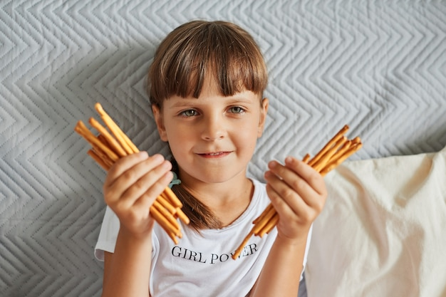 Portrait of charming dark haired girl holding pretzels sticks in hands and looking directly at camera, female child wearing white t shirt, has pigtails, posing at home while sitting on sofa.