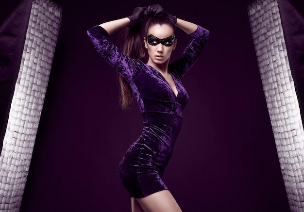 Ritratto di affascinante donna bruna elegante in un bellissimo vestito viola e maschera di paillettes