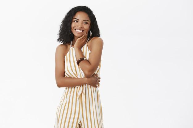 Portrait of charming elegant dark-skinned female enjoying wearing cute yellow striped overalls touching face gentl