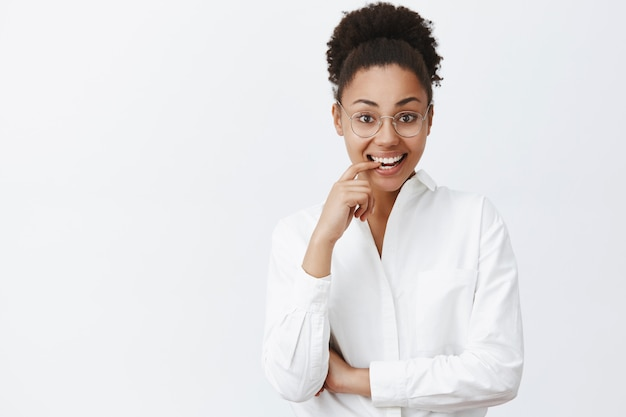 Portrait of charming emotive and feminine dark-skinned female tutor in white-collar shirt and glasses, biting finger from curiosity and smiling broadly, gazing intrigued and interested