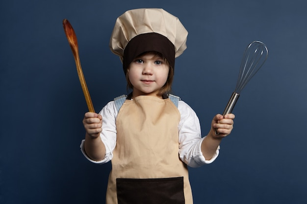 Portrait of charming female child chef or cook holding kitchen utensils, ready to make dinner. cute little girl in hat and apron using wire whisk and wooden spoon while cooking in kitchen with her mom