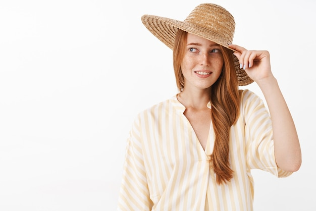 Portrait of charming and feminine redhead female in striped summer blouse touching cap gazing with pleased smile left walking over gray wall