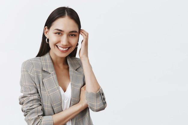 Ritratto di affascinante flirty adulto donna abbronzata in abiti alla moda, toccando delicatamente i capelli e sorridendo ampiamente, arrossendo sul muro grigio