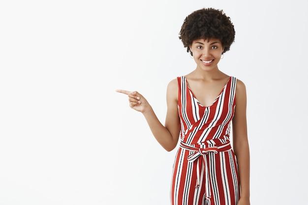 Ritratto di affascinante flirty e audace bella donna afroamericana con acconciatura afro che punta a sinistra e sorridente con espressione intrigata e curiosa che mostra interessante spazio di copia