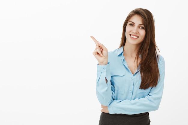 Ritratto di affascinante amichevole bruna imprenditrice posa in studio