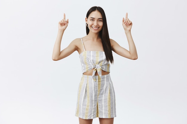 Portrait of charming friendly and stylish woman with long dark hair and mole under lip, smiling broadly while raising hands and pointing upwards