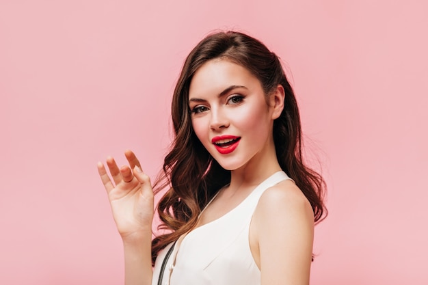 Portrait of charming green-eyed brunette woman with red lips dressed in white top on pink background.