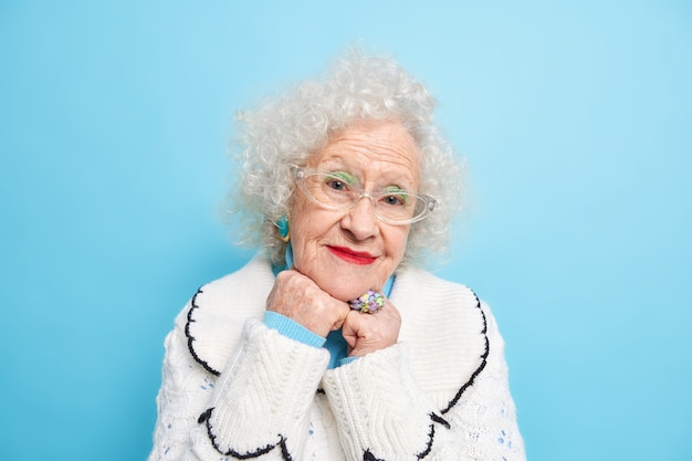 Portrait of charming grey haired female pensioner keeps hands under chin looks with pleased expresion, listens pleasant words being happy wears casual jumper