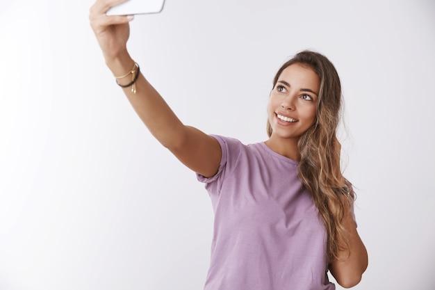肖像画の魅力的な幸せな女の子の旅行者観光自撮り笑顔ポーズ白い壁を拡張ハンドキャプチャアッパーアングル写真、スマートフォンを保持し、旅の写真を共有するインターネットフォロワー