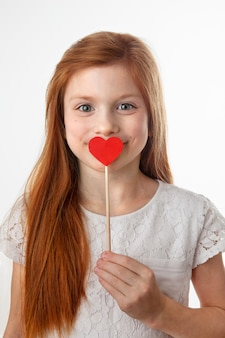 Portrait of charming happy red-haired girl covering her mouth with red paper heart on stick and smiling at camera. symbol of kiss and love, valentines day, mothers day or fathers day concept,