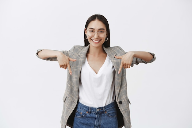 Portrait of charming happy young entrepreneur in eyewear and stylish jacket, pointing down with raised hands and smiling with self-assured satisfied expression