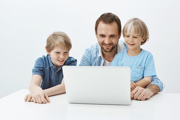Ritratto di affascinante gioioso padre europeo seduto con figli vicino al computer portatile, guardando lo schermo con un ampio sorriso mentre abbraccia il ragazzo e si diverte a trascorrere del tempo nella cerchia familiare