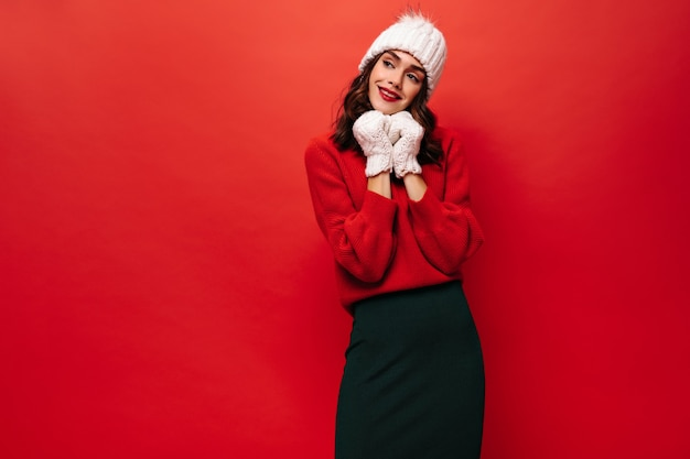 Portrait of charming lady in black skirt, bright sweater, knitted hat and mittens smiling and posing on red wall