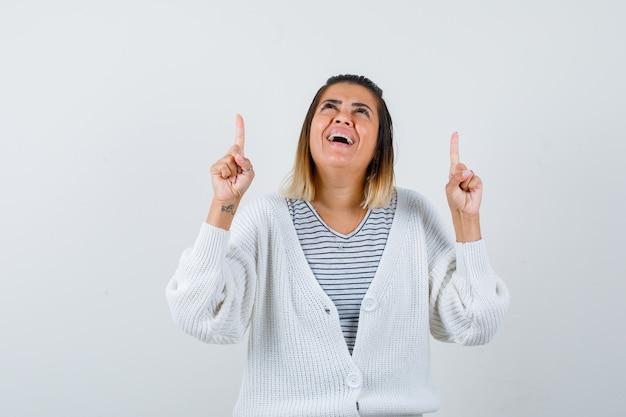 Ritratto di una donna affascinante che punta verso l'alto, guarda in alto in maglietta, cardigan e sembra felice