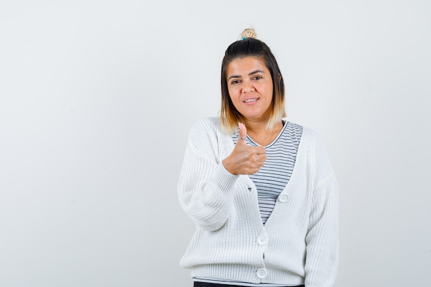 Ritratto di una donna affascinante che mostra il pollice in su in maglietta, cardigan e sembra una vista frontale allegra