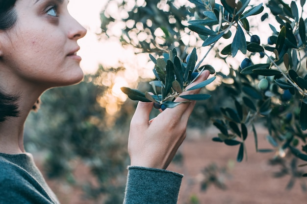 Ritratto di signora affascinante in abito resort estivo in posa accanto all'olivo