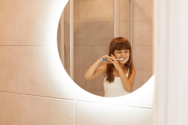 Portrait of charming little female kid brushing teeth in bathroom, squeezing toothpaste out of a tube, standing in front of the mirror, having concentrated facial expression.