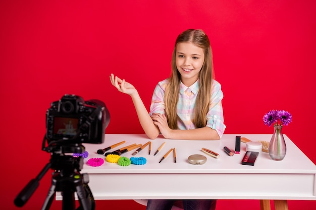 Portrait of charming little girl filming herself at the table with cosmetics