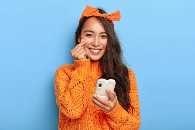 Portrait of charming lovely lady in stylish orange clothes, makes korean heart sign, expresses her love and sympathy, uses mobile phone for shopping online