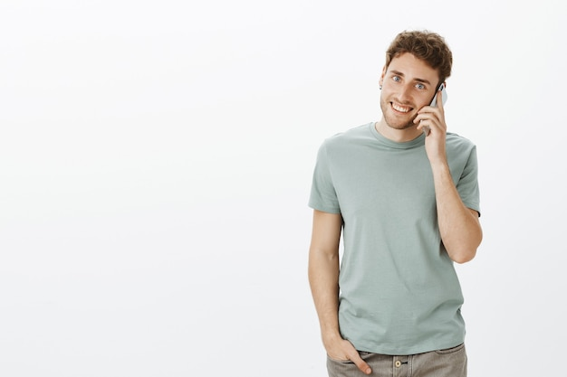 Portrait of charming outgoing fair-haired male with bristle, holding hand in pocket while waiting for mom to pick up phone, calling and holding smartphone near ear