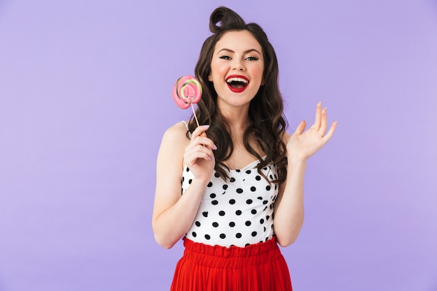 Portrait of charming pin-up woman in vintage polka dot dress smiling while holding and eating colorful lollipop isolated over violet wall