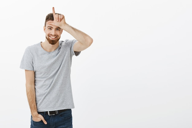 Portrait of charming playful and masculine european male with beard, blue eyes and moustache holding hand in jeans showing letter l over forehead as if mocking friend making loser gesture and grinning