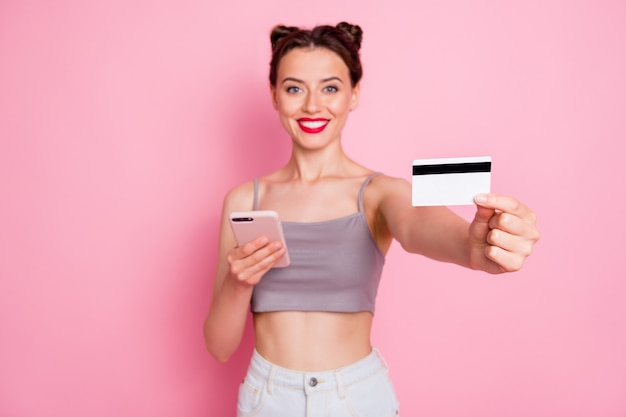 Portrait of charming positive girl use smartphone online shopping user pay purchase with credit card  advise summer wear grey white clothing isolated over pink color