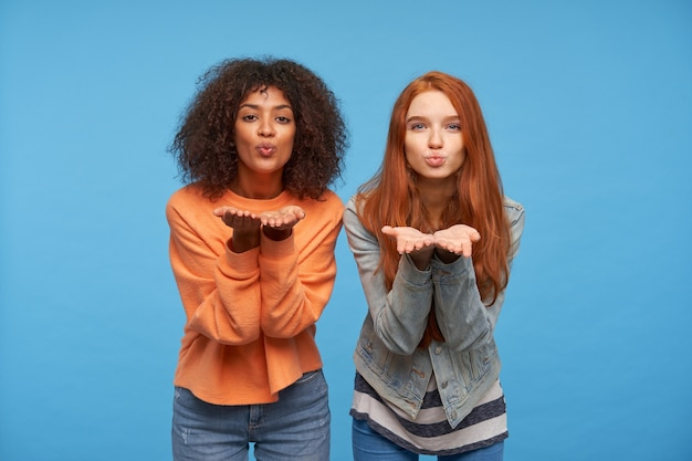 Portrait of charming positive pretty young women raising their palms while posing over blue wall, folding their lips and blowing air kiss