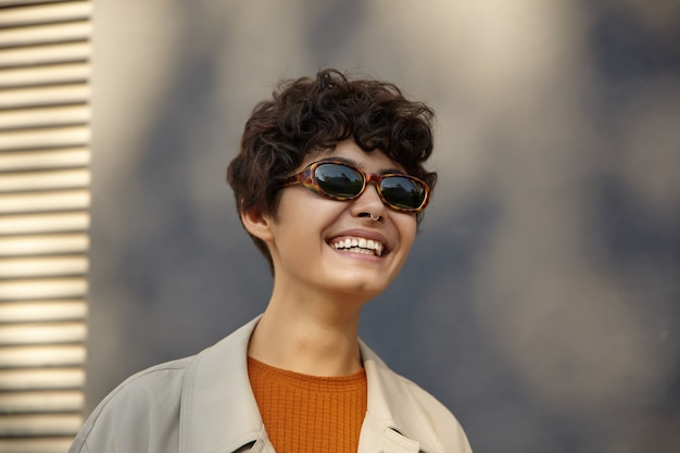 Portrait of charming positive young brunette woman with short haircut smiling happily while standing over urban environment in stylish clothes and vintage sunglasses