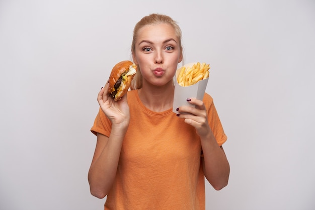 Portrait of charming pretty young blonde woman holding junk food and looking joyfully to camera, puffing out cheeks and being excited about tasty dinner, isolated over white background