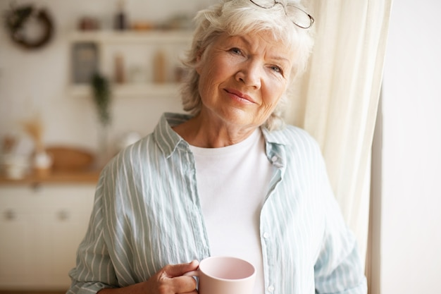 Portrait of charming relaxed female on retirement having morning coffee indoors, standing in kitchen by window with cup in her hands, looking with joyful radiant smile. people and lifestyle