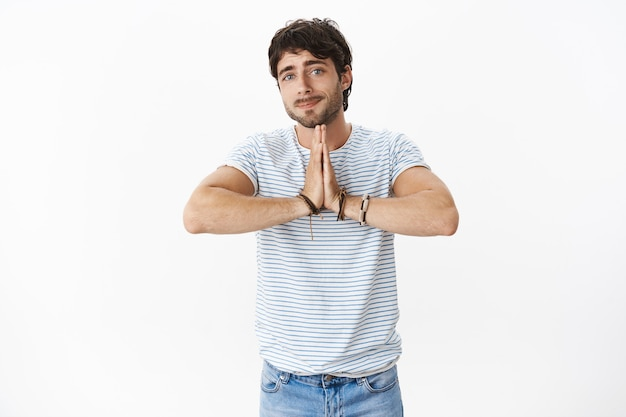Portrait of charming and sincere guy with beatiful blue eyes and bristle showing begging gesture, holding hands in pray and smiling cute at front to ask for favour