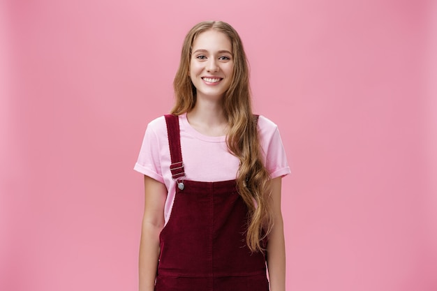 Portrait of charming slim young girl with long fair hair in corduroy overalls smiling joyfully standing upright with positive grin posing against pink background happy and friendly.