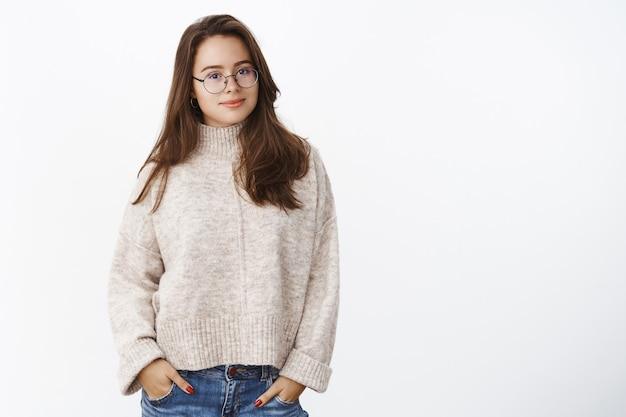 Portrait of charming smart and confident brunette in glasses wearing sweater, holding hands in pockets smiling cute at front as posing against gray wall.