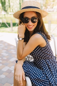 Portrait of charming style woman in the summer park wearing summer hat and black sunglasses and cute dress.