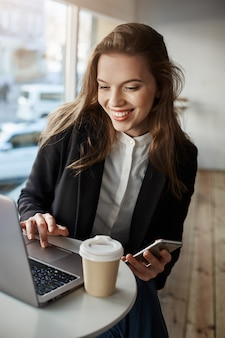 Portrait of charming stylish woman in cafe, browsing in net via laptop, holding smartphone and drinking tea, using free wifi and enjoy free time