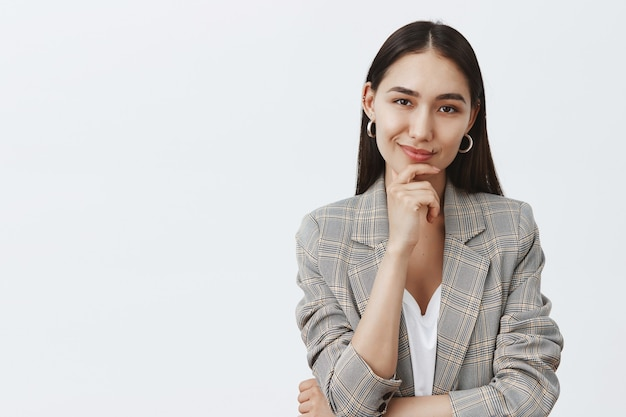 Portrait of charming successful female in stylish jacket over t-shirt, holding hand on chin and smirking while having great idea in mind, thinking about something curious over gray wall
