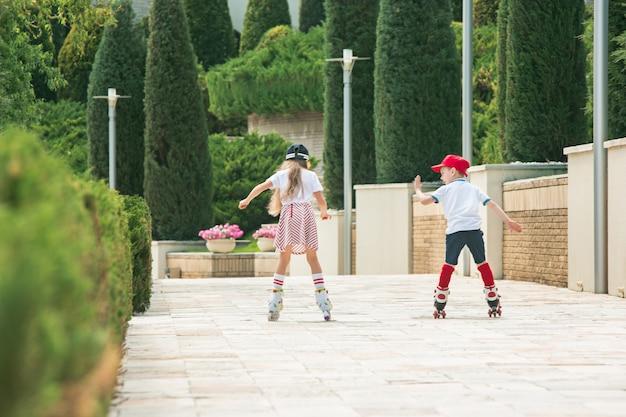 Ritratto di un'affascinante coppia di adolescenti che pattinano insieme sui pattini a rotelle al parco. ragazzo e ragazza caucasici teenager
