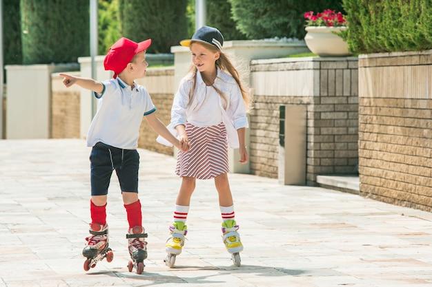Portrait of a charming teenage couple skating together on roller skates at park.