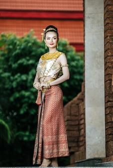 아름 다운 전통 드레스 의상, 고고학 사이트 또는 태국 사원, 태국의 정체성 문화에서 전형적인 타이어 드레스를 입고 초상화 매력적인 태국 여자