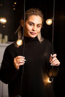 Ritratto di donna affascinante in maglione nero in piedi e in posa