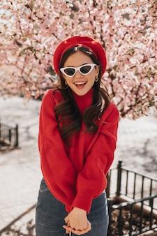Ritratto di donna affascinante in berretto rosso e occhiali su sfondo di sakura. signora in jeans e maglione luminoso che gode della passeggiata nel giardino fiorito