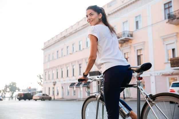 Portrait of a charming woman riding on bicycle in city street
