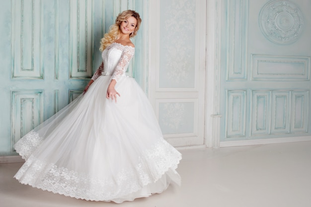 Portrait of charming woman in wedding dress. dancing on the walls with classic moldings