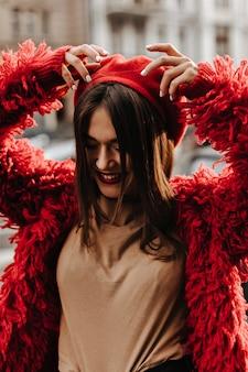 Ritratto di donna affascinante con labbra rosse, vestita di eco-cappotto rosso e berretto. signora di ottimo umore cammina per la città.