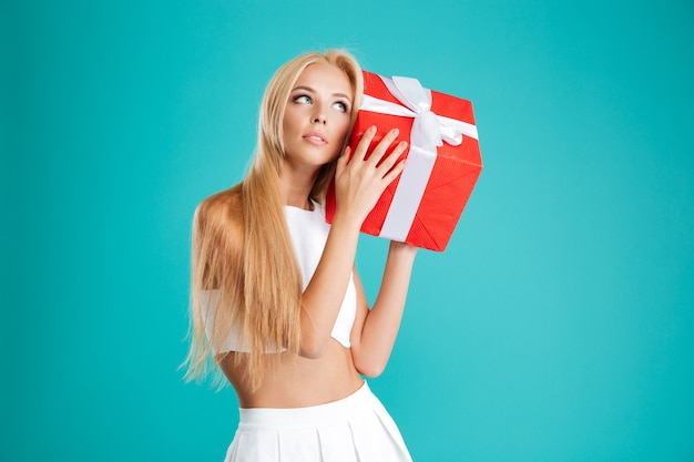 Portrait of a charming wondering woman holding gift box at her ear over blue background