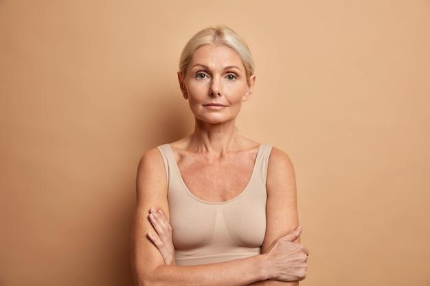 Ritratto di affascinante donna rugosa in posa con le braccia incrociate