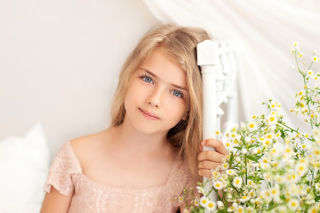 Portrait of charming young blonde with long hair. little girl and daisies on bed in a bright bedroom in morning.