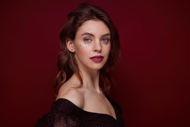 Portrait of charming young brunette lady with wavy hairstyle wearing evening makeup while posing over claret background, dressed in festive clothes with deep neckline